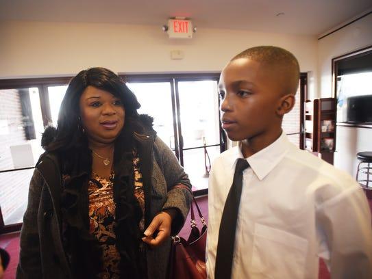 Jaden Clarke, 11, of Union is interviewed as his grandmother