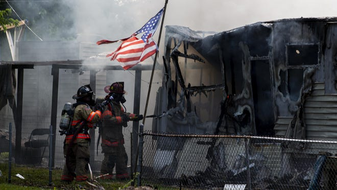 Springfield firefighters fight a fire that has fully engulfed a  mobile home and a RV parked next to it on North 30th Street, Friday, June 26, 2020, in Springfield, Ill. The mobile home was fully involved with heavy smoke when firefighters arrived and it destroyed the mobile home an RV and damaged an adjacent home.