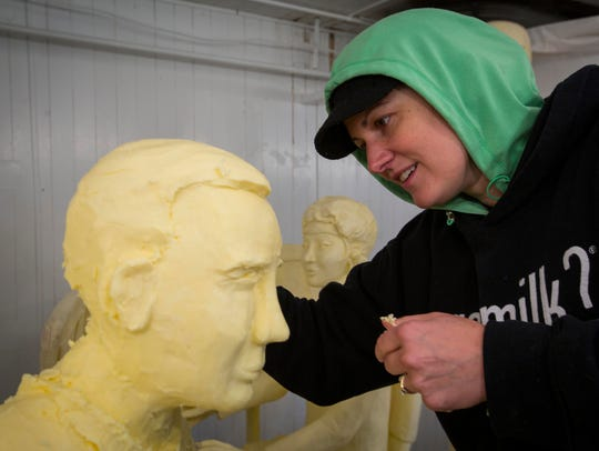 Butter sculptor Sarah Pratt works on the head of Captain