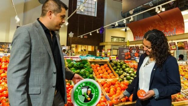 Gerardo Reyes Chavez of the Coalition of Immokalee Workers and Felis Andrade of Giant Food place a Fair Food sign next to tomatoes in Giant's O Street store in Washington, D.C.