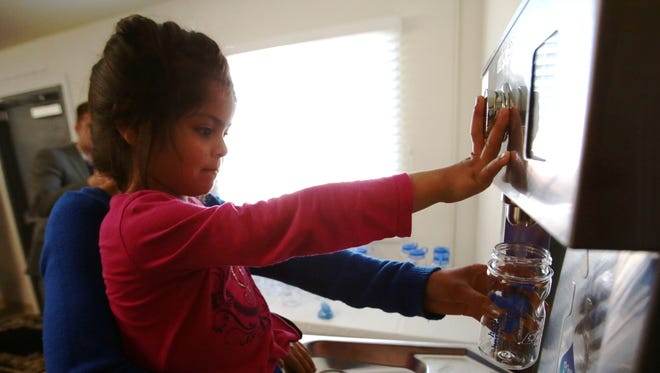 """Alannie Rodriguez, 4, fills her water bottle from a new fountain with the help of her aunt, Gabriela Rodriguez. The """"tap"""" at the San Jose Community and Bea Learning Center in Thermal is one of seven unveiled Wednesday."""