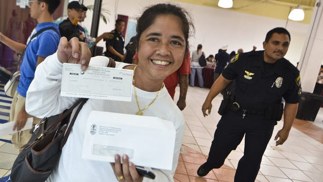 In this Dec. 3, 2011, file photo, Tamuning resident Mila Santo displays her past-due tax refund check at the Micronesia Mall in Dededo. The refunds were paid using $198 million the government of Guam borrowed on the bond market. The following year, $60 million more was borrowed for refunds. About 21,000 residents, desperate for their refund checks, lined up in early December 2011 to receive them early. The balance of 63,000 refund checks was mailed.