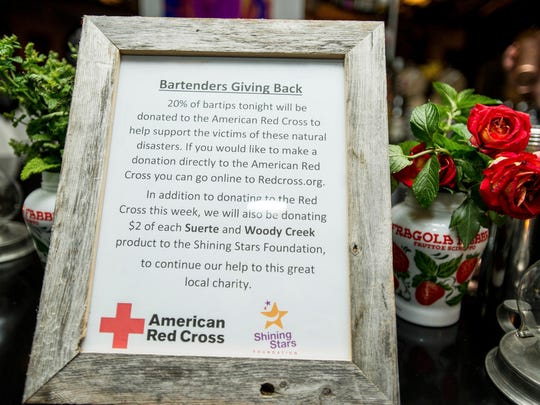 In this Thursday, Sept. 28, 2017, photograph, a sign sits on the bar of the Chef's Club in Aspen, Colo., to inform patrons that a percentage of their tips for bartender Zach Bowersock would be given to organizations to help the victims of natural disasters. (Anna Stonehouse/The Aspen Times via AP)