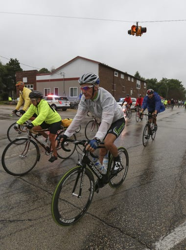 Riders pass through the rain on Friday, July 25, 2014, in Bremer, Iowa.