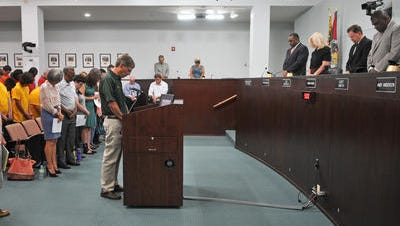In a July 2015 photo, Chaplain Roger Alexander of the Brevard County Sheriff's Office delivers the invocation at the Brevard County Commission meeting.  Shortly after that, a lawsuit was filed by atheists and agnostic organizations, protesting the county's policy on allowing only religious representatives to give the innovation.