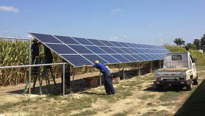 In this Sept. 6, 2013 photo provided by Austin Ridgley, workers erect some of the 90 solar panels at Timothy Ridgely's 2,700-acre southeastern Illinois farm in Parkersburg, Ill. Thousands of farms and other small businesses across America have begun embracing renewable energy to cut costs and boost their often uncertain bottom lines, often with the help of a federal program.