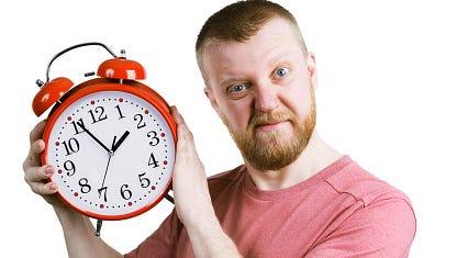 Impatient man holds a clock
