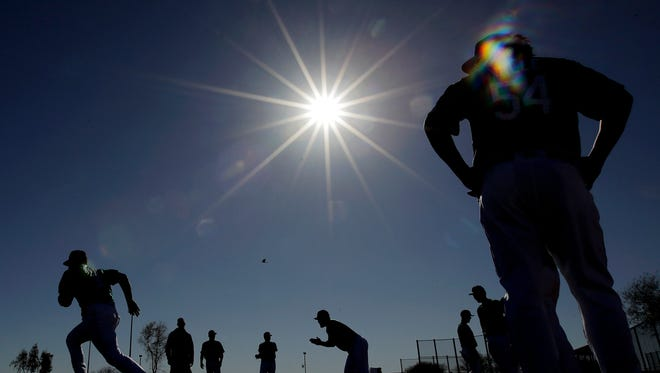 Mariners pitchers run sprints during a spring training workout in Peoria, Ariz.