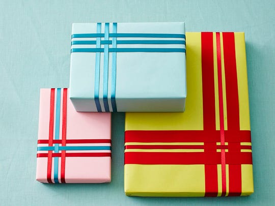 In this photo provided by Better Homes and Gardens, for gifts that need to be shipped or stacked flat, weave differently sized and colored ribbons in a simple pattern –crossing one ribbon over another – and attaching in back. Or use washi tape, which comes in so many colors and holiday-themed patterns.