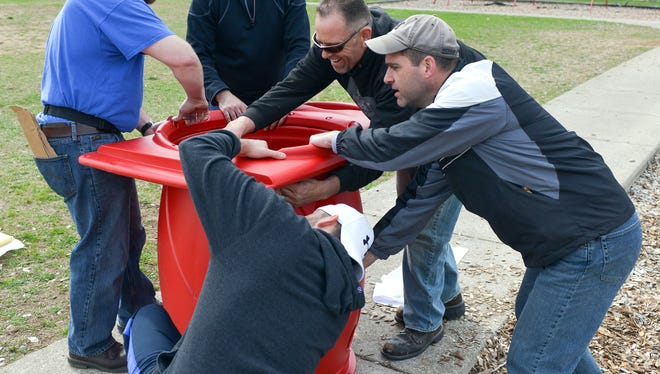 Volunteers work to put together a section of the tunnel for the K-2 playground structures at Minges Brook Elementary Saturday morning.