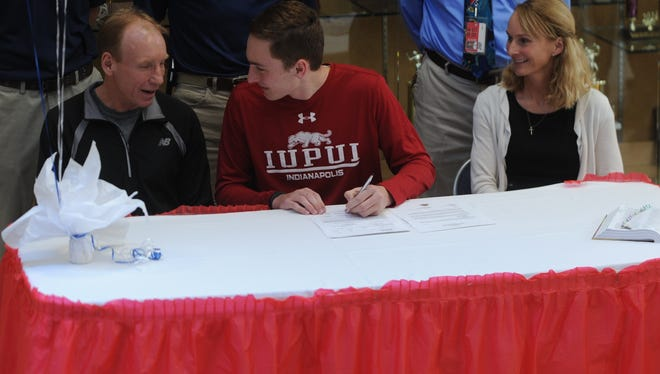 Seton Catholic's Jacob Stamm, seated with parents Chris, left, and Shaunna, signs his national letter of intent on Wednesday to compete in cross country and track and field for IUPUI.