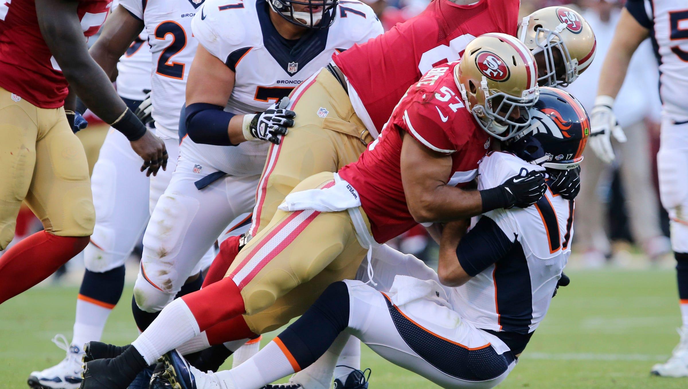 San Francisco 49ers linebacker Michael Wilhoite (57) and tight end Demarcus Dobbs (83) sack Denver Broncos quarterback Brock Osweiler (17) during the second quarter at Candlestick Park.