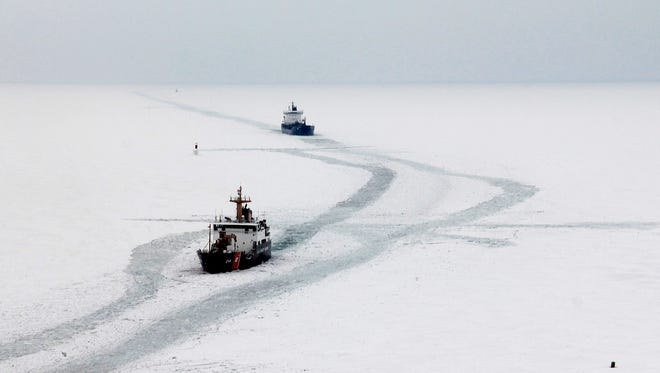 In a Feb. 19, 2014 photo, the Cutter Hollyhock cuts a track line for the motor vessel Algosea in Lake St. Clair, Mich. The Coast Guard's nine Great Lakes icebreakers have put in four times as many icebreaking hours this year due to frigid winter weather.