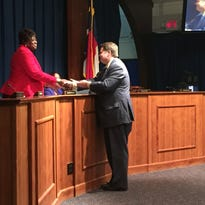 David Gantt, chairman of the Buncombe County Board of Commissioners, presents a letter from commissioners to Jacquelyn Hallum, outgoing chair of the Asheville City Board of Education. Hallum and fellow board member Precious Grant were recognized for their service on the board. Their terms are ending.