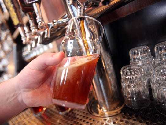 A Centennial IPA is poured at Founders Brewing in Grand