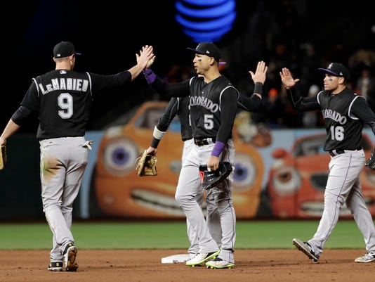 Colorado Rockies' D.J. LeMahieu (9) Carlos Gonzalez (5) and Stephen Cardullo (16) celebrate after the team's 3-1 win over the San Francisco Giants during a baseball game, Thursday, April 13, 2017, in San Francisco. (AP Photo/Marcio Jose Sanchez)ww