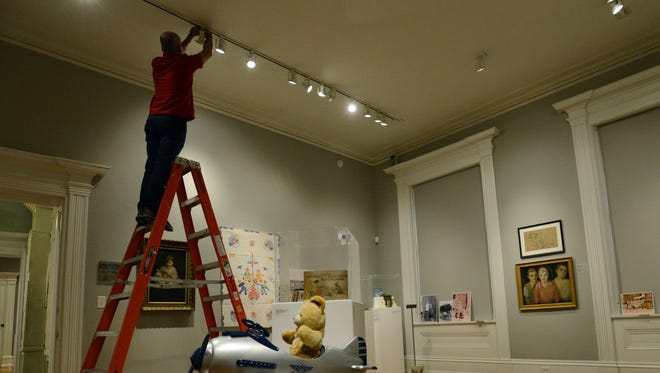 Chris Miller, a member of the Decorative Arts Center of Ohio's exhibition team, sets lights for the museum's new exhibit An Ohio Childhood: 200 Years of Growing Up. The exhibition, which opened Friday, features toys and art that depicts childhood.