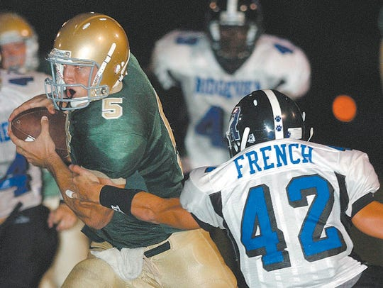 Nease quarterback Tim Tebow slips around Ridgeview's