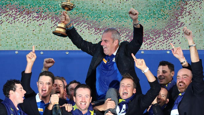 Europe players lift their captain Paul McGinley as he holds the trophy after winning  the 2014 Ryder Cup golf tournament, at Gleneagles, Scotland, Sunday.