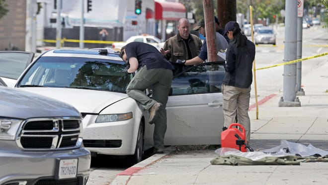 Investigators record the scene from a car belonging to a heavily armed man after he was arrested in Santa Monica, Calif., early Sunday, June 12, 2016. The man reportedly told police he was in the area for West Hollywood's huge gay pride parade. Authorities did not know of any connection between the gay nightclub shooting in Orlando, Fla., early Sunday and the Santa Monica arrest. (AP Photo/Reed Saxon)