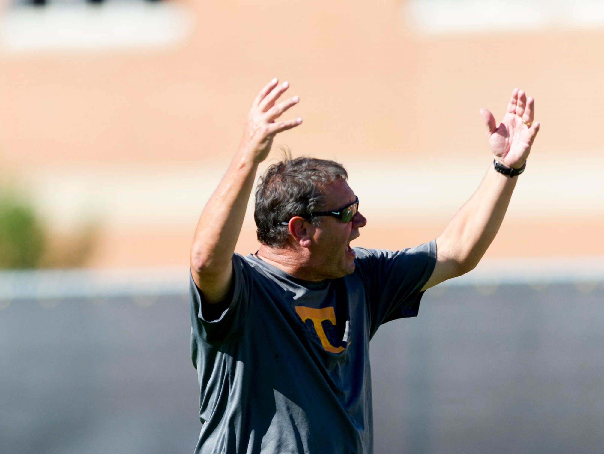 Offensive line coach Brady Hoke calls to players during Tennessee fall football practice at Anderson Training Facility in Knoxville, Tennessee on Thursday, August 24, 2017.