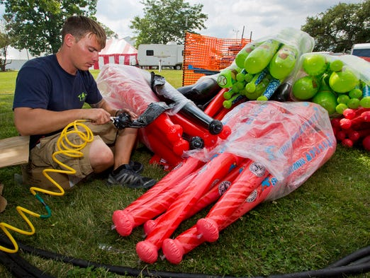 Henry Johns with Luehr's Carnival and Rides blows up prizes that will be used at the Tippecanoe County 4-H Fair Friday, July 18, 2014, in Lafayette. The fair opens Saturday with the Queen contest at 8 p.m. in the coliseum.