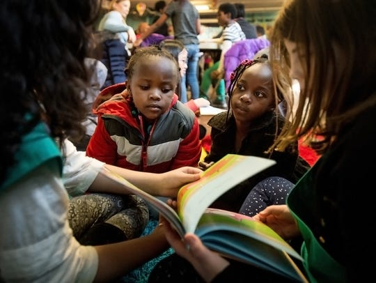 Germantown Girl Scouts Emma Gaur, 9, left, and Bella Langdridge, 9, right, read a story to Emily, 4, center left, and Aime, 6, during a read-a-thon event at Refugee Empowerment Program on Jan. 15.