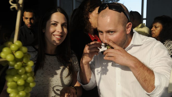 Jennifer Fink, left of Voorhees and Andrew Benner of Berlin Sample the cuisine  at Taste of South Jersey, sponsored by Camden County Regional Chamber of Commerce in June 2014 at the Adventure Aquarium in Camden NJ.