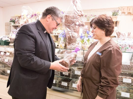 The Rev. Joseph Blenkle, left, looks at a chocolate bunny with Sally Craft at Alps Sweet Shop in Fishkill on Friday, April 7, 2017.