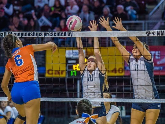 Piedra Vista's Kamryn Gordon (10) and Autumn Begay (11) block a spike from Los Lunas' Jordan Holland during the quarterfinals of the 5A volleyball tournament Friday at the Santa Ana Star Center in Rio Rancho.