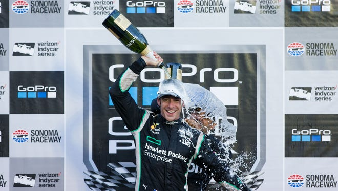 Sep 18, 2016; Sonoma, CA, USA; Hewlett Packard Enterprise driver Simon Pagenaud puts champagne on himself to celebrate his title at the GoPro Grand Prix of Sonoma at Sonoma Raceway. Mandatory Credit: John Hefti-USA TODAY Sports