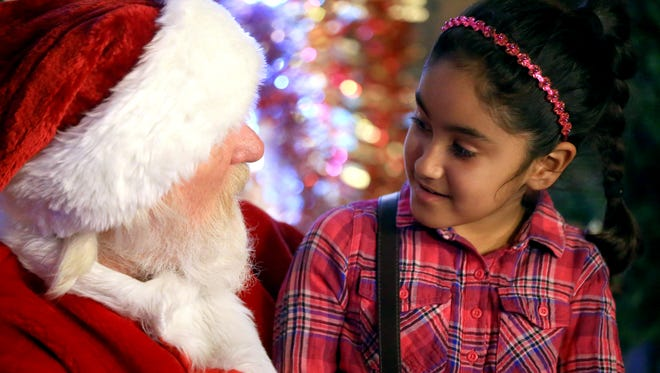 Ana Riuz talks to Santa Claus while visiting the annual Candy Cane Lane holiday light display with her family on Saturday, Dec. 17, 2016, in Corpus Christi.