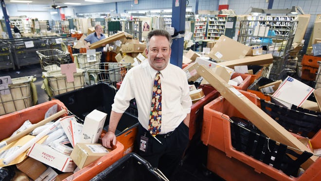 Madison Postmaster Nathan Dunaway is surrounded by parcels, packages and other mail as the holiday season reaches full swing.