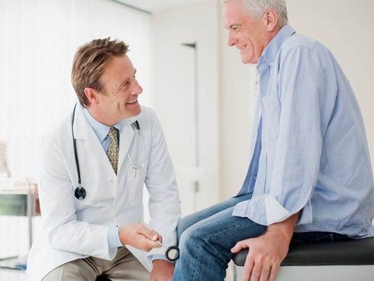 Doctor checking patients reflexes in doctors office