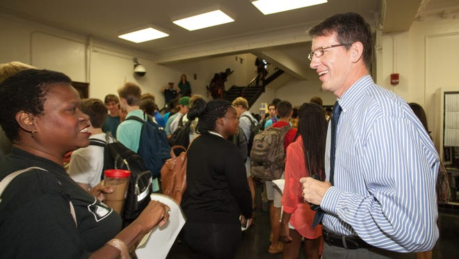 Leon High School principal Billy Epting, right, greets students and staff members in 2014.