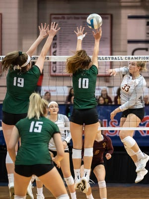 """Farmington Hills""""s Jess Mruzik (33) drills one over the Lake Orion blockers Kendall Robertson (19) and Wren Macauley (10) during MHSAA Volleyball semifinals at Kellogg Arena in Battle Creek on Friday."""