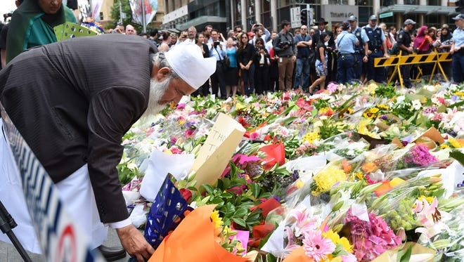 A Muslim man and a relative join thousands of Sydneysiders in laying flowers near the Lindt chocolate cafe in Martin Place following last the dramatic siege in Sydney on Dec. 16.
