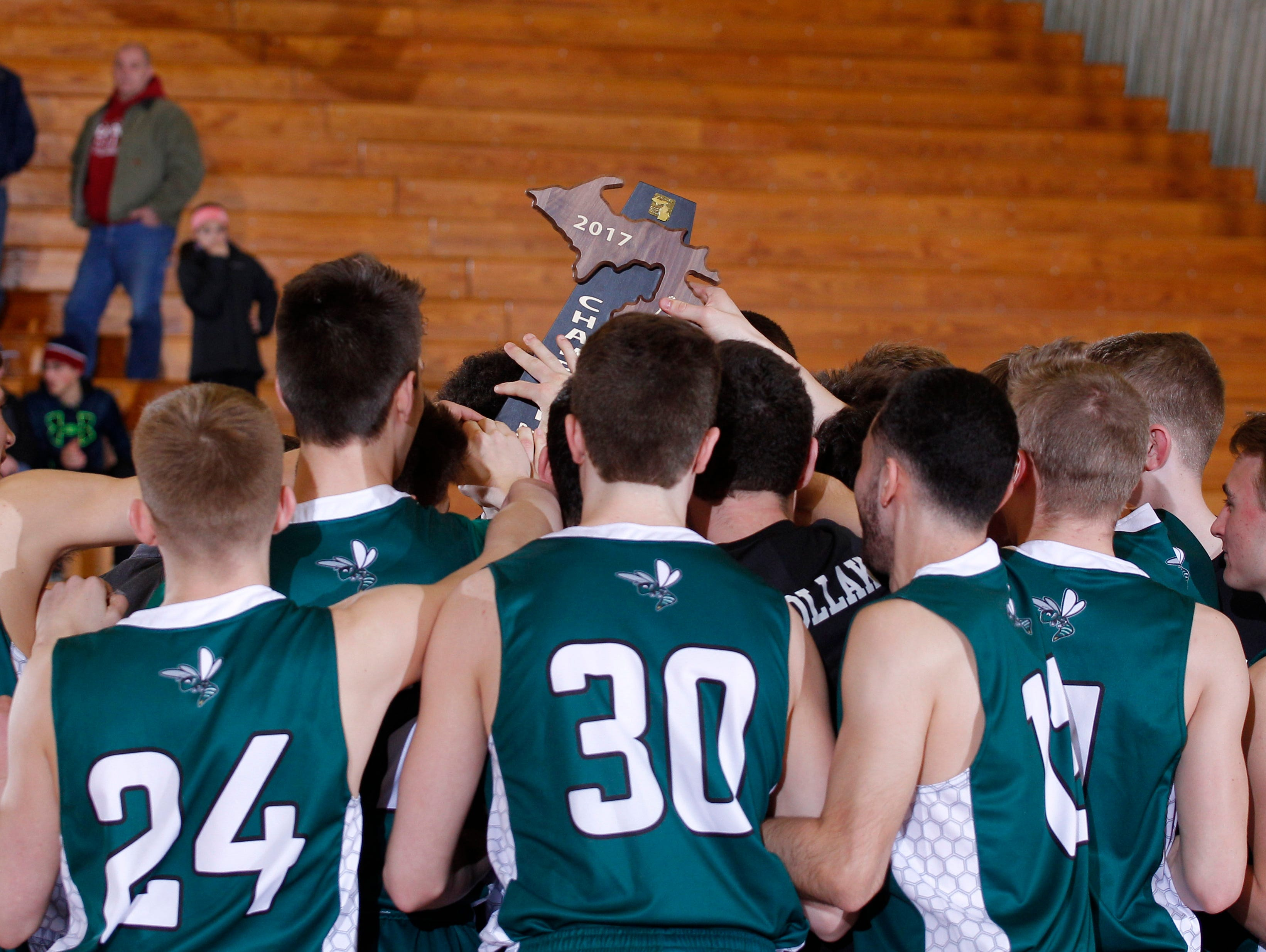 Williamston players celebrate with their regional championship trophy after defeating Portland 51-40, Wednesday, March 15, 2017, in Ionia, Mich.