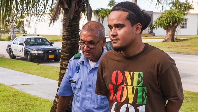 Suspect Riality Joe, 21, is escorted from the Guam Police Department precinct in Hagåtña after his arrest on Thursday, July 13, 2017.
