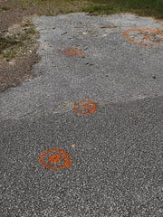 Spray paint marks where police collected evidence on the ground off of Pleasant Creek Lane in Bolivar, Tenn., on Thursday, Sept. 15, 2016.