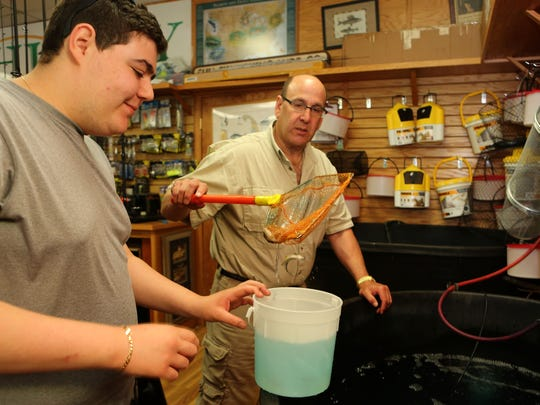 Dan Agate, 19, of New City purchases live bait from owner Skip Storch at Shu-Fly Tackle & Fly Shop in Nanuet, June 1, 2016.