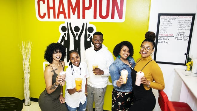 Owner Radira Mendes, second from left, and the staff at 508 Champion Nutrition located at 1 Centre St. in downtown Brockton smile for a photograph on Thursday, June 11, 2020.