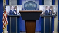 President Obama is seen on screens in the White House