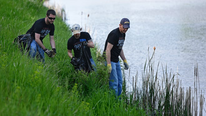 Lee Clemens, Ryan Oorlog and Eric Turner cleanup the Big Sioux River near Sherman Park along the bike path in Sioux Falls, S.D., Saturday, May 21, 2016.