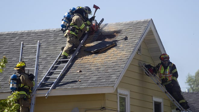 Firefighters cut a hole in the roof of a home on West Pearl Street in Stevens Point to ventilate smoke from the house. Firefighters from the Stevens Point, Plover, and Hull fire departments responded to the Thursday, July 30 fire.