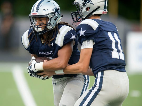 Farragut quarterback Gavin Wilkinson hands the ball off to Isaiah Gibbs during the game against Morristown West at Farragut on Thursday, August 31, 2017.