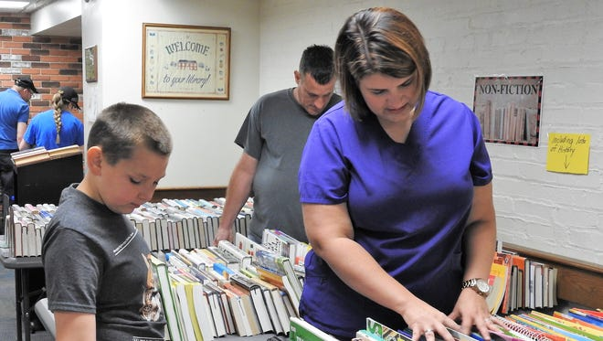 Jarome Starner, 10, and his mother, Leslie Ridenbaugh peruse books at the Friends of the Library annual book sale on Thursday. The sale continues Friday and Saturday.