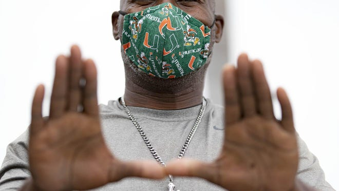 Earl Sanders, of West Palm Beach, wears a University of Miami mask his son's friend made for him as he enters Walmart in Royal Palm Beach on Monday.