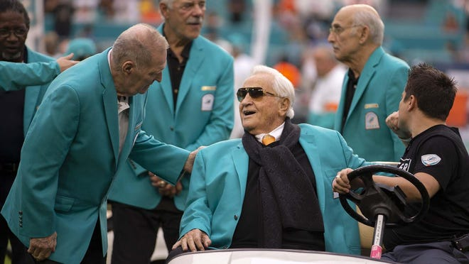 Coach Don Shula talks with Jim Kiick (left) with Larry Csonka and Manny Fernandez in the background. The Miami Dolphins 1972 team celebrated being named the best NFL team ever during a halftime ceremony at Hard Rock Stadium in Miami Gardens, Dec. 22, 2019.