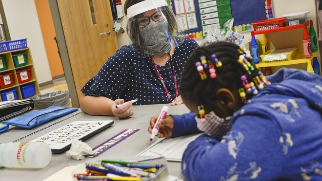 Heather McGill helps kindergartener Nevaeh Murphy with her letters on the first day of school at Godley Station School on Monday morning. Steve Bisson/Savannah Morning News.